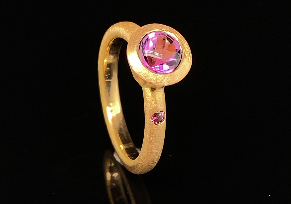 large purple diamond set in yellow gold